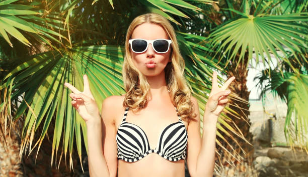 Summer portrait young woman showing peace sign gesture blowing lips sending sweet air kiss over palm tree background stock photo