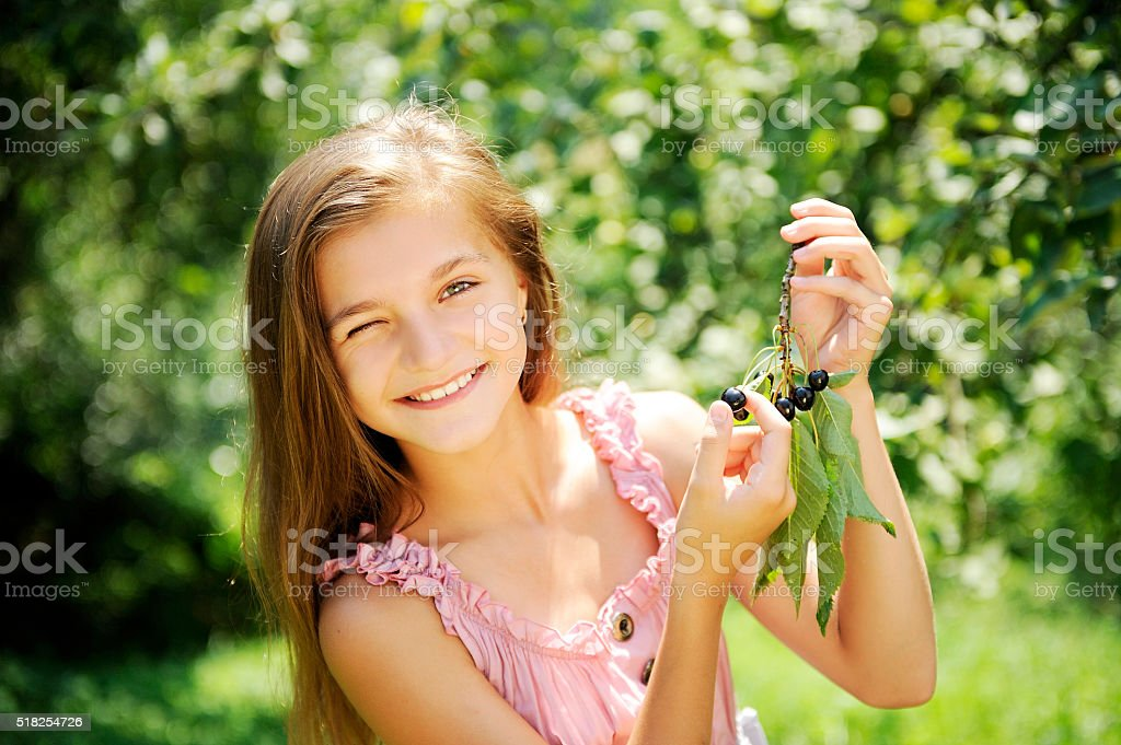 Summer, preteen girl in the garden, branch with black cherries. stock photo