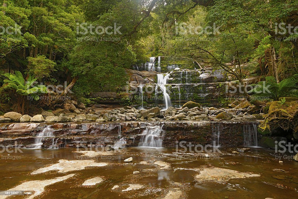 Summer rain cascades over rocky waterfall in rainforest royalty-free stock photo
