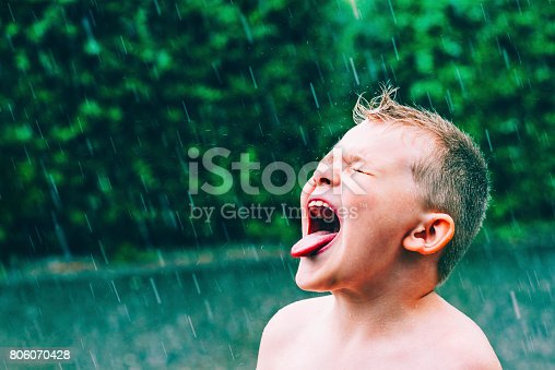 Boy stands outside as the rain pours down. He sticks out his tongue to taste the water falling from the sky.