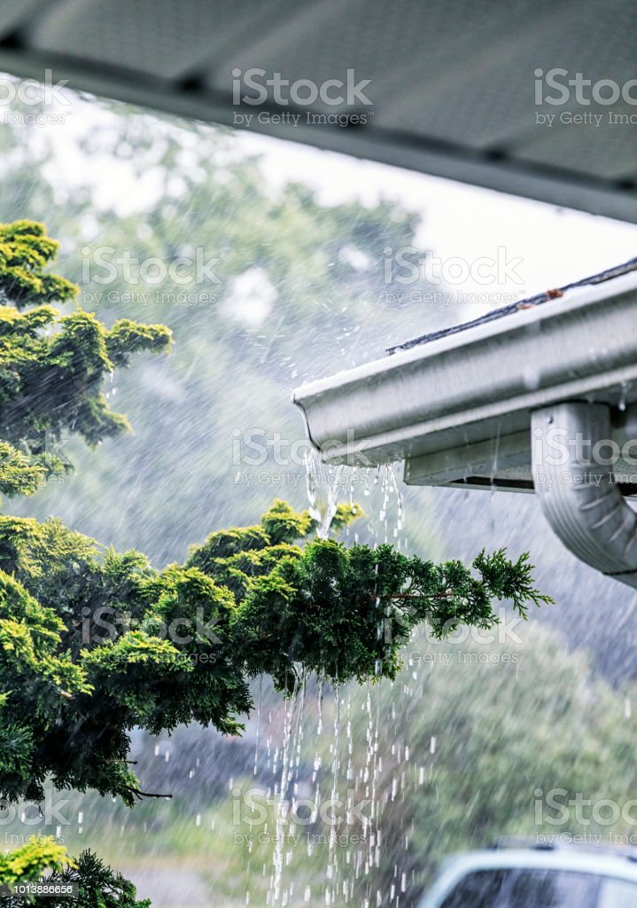 Drenching, gushing rain storm water is rushing and splashing off the...