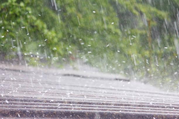 pluie d'été avec la grêle tombe sur le toit d'ardoise - endommagé photos et images de collection