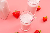 istock Summer refreshing desserts and calcium rich healthy drink concept theme with glasses of strawberry milk, glass bottle, striped straws and scattered strawberries isolated on pink background 1198973010