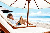 Summer Relaxation. Beautiful Woman Reading E-Book, Relaxing On Sun Lounger, Deck Chair Under Umbrella, Tent On Beach By Sea. Summertime. Holiday Vacations. Leisure, Recreation, Enjoyment Concept