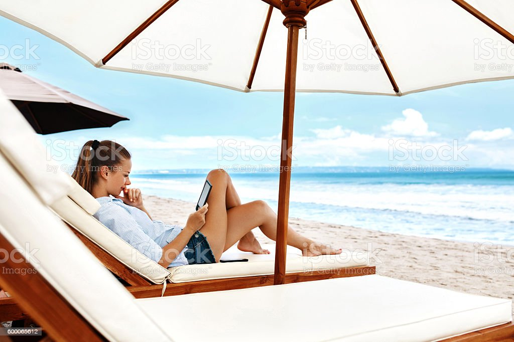 Summer Relaxation. Woman Reading, Relaxing On Beach. Summertime stock photo