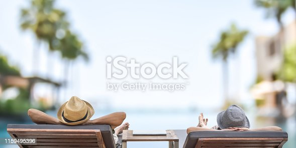 istock Summer resort hotel stay relaxation with tourist traveller couple take it easy happily resting on beach chair on holiday travel vacation poolside peacefully at tropical beach swimming pool 1159495396