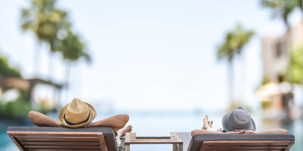 Summer resort hotel stay relaxation with tourist traveller couple take it easy happily resting on beach chair on holiday travel vacation poolside peacefully at tropical beach swimming pool Summer resort hotel stay relaxation with tourist traveller couple take it easy happily resting on beach chair on holiday travel vacation poolside peacefully at tropical beach swimming pool affluent lifestyles stock pictures, royalty-free photos & images