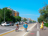 Rimini, Italy - September 1, 2019: Long street along the sea at the tourist resort of Rimini. A man and a child ride bicycles. Behind the men is a rubber ring for swimming. Nearby, two women go to the beach.