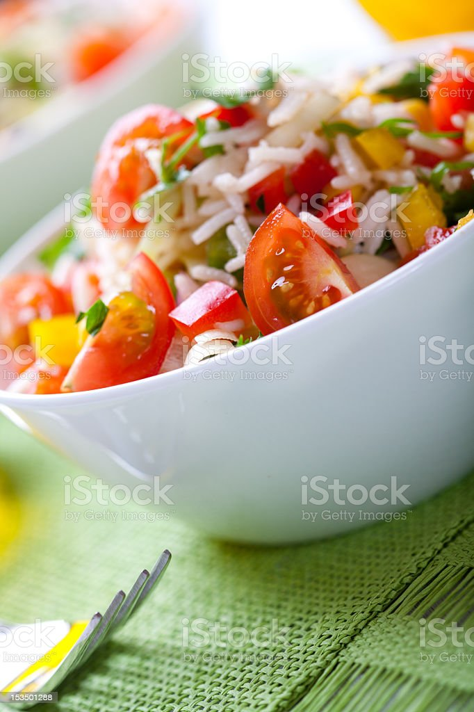 Summer rice salad with vegetables and fresh herbs stock photo
