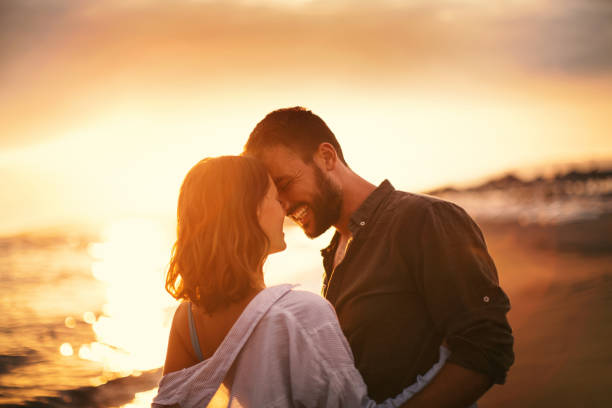 Summer romance. Young couple looking each other on the beach at late sunset. Love is in the air. They are about to kiss. romantic activity stock pictures, royalty-free photos & images
