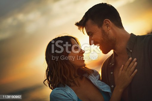 Young couple looking each other on the beach at late sunset. Love is in the air. They are about to kiss.