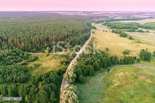 1155573645 istock photo Summer rural landscape, aerial view. View of green fields and country road 1209716912