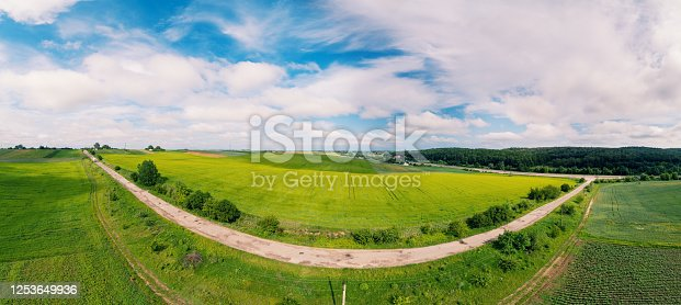 1155573645 istock photo Summer rural landscape, aerial view. View of green fields, forest, village and highway 1253649936