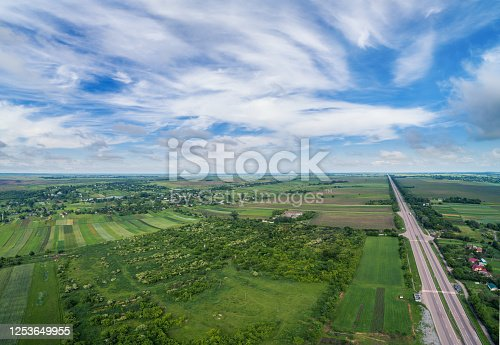 1155573645 istock photo Summer rural landscape, aerial view. View of green fields, forest, village and highway 1253649955