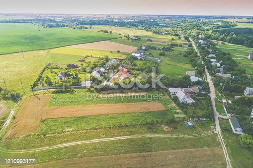 1155573645 istock photo Summer rural landscape. Aerial view. View of green fields, village, and country road 1210993177