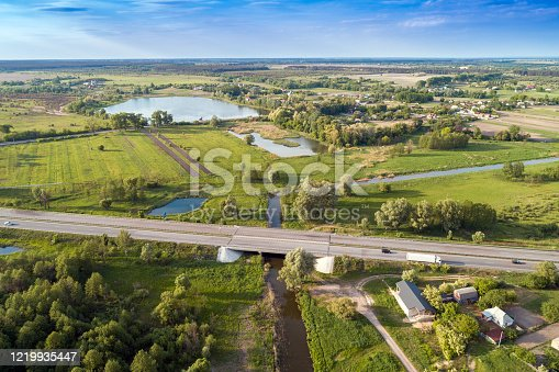 1155573645 istock photo Summer rural landscape, aerial view. View of green fields, village and highway 1219935447