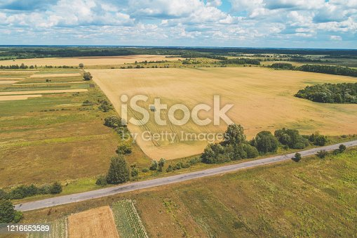 1155573645 istock photo Summer rural landscape. Aerial view. View of the village and arable fields with beautiful sky 1216653589