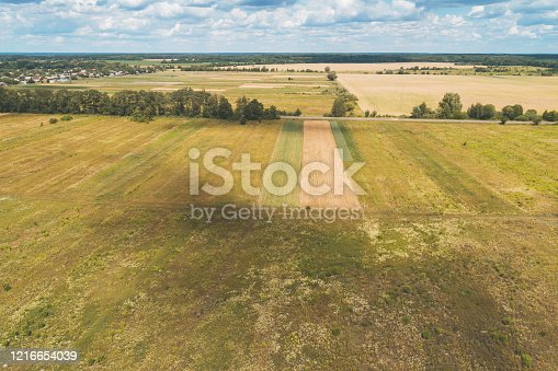 1155573645 istock photo Summer rural landscape. Aerial view. View of the village and arable fields with beautiful sky 1216654039
