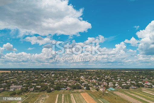 1155573645 istock photo Summer rural landscape. Aerial view. View of the village and arable fields with beautiful sky 1216654058