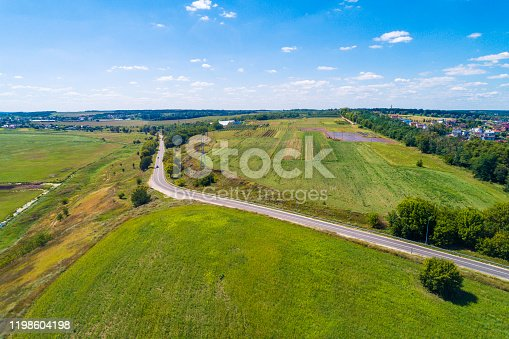 1155573645 istock photo Summer rural landscape, aerial view. View of the village, green fields, and road 1198604198