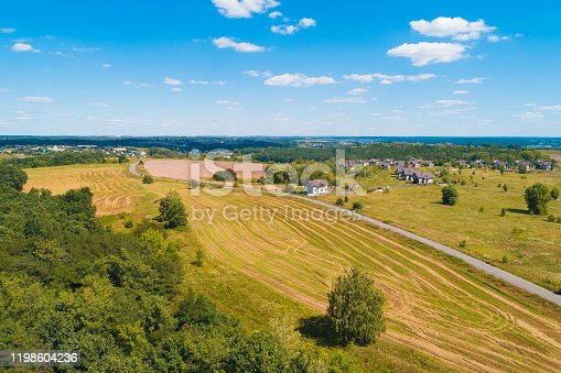 1155573645 istock photo Summer rural landscape, aerial view. View of the village, green fields, and road 1198604236
