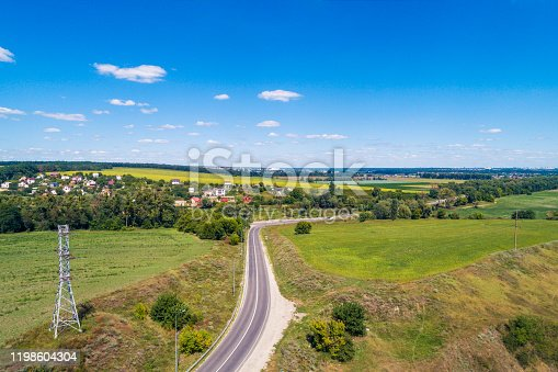 1155573645 istock photo Summer rural landscape, aerial view. View of the village, green fields, and road 1198604304