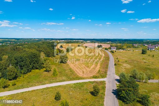 1155573645 istock photo Summer rural landscape, aerial view. View of the village, green fields, and road 1198604342