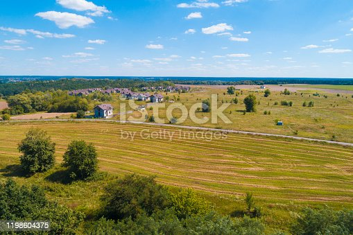 1155573645 istock photo Summer rural landscape, aerial view. View of the village, green fields, and road 1198604375