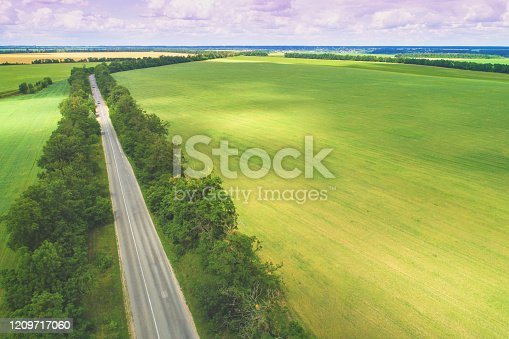 1155573645 istock photo Summer rural landscape. Aerial view. View of the village, green fields, and road 1209717060