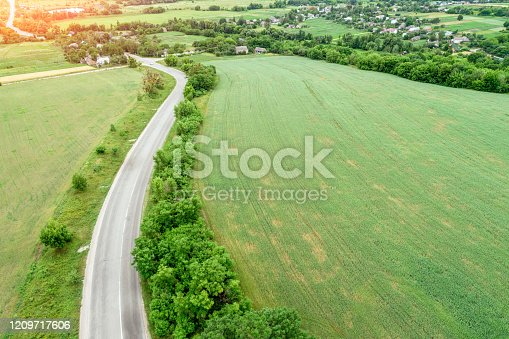 1155573645 istock photo Summer rural landscape. Aerial view. View of the village, green fields, and road 1209717606