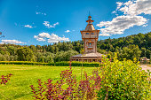 Summer rural landscape. Old wooden Church on a green meadow on a Sunny summer day against a green forest and blue sky. The concept of peace and tranquility.