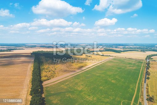 1155573645 istock photo Summer rural landscape, view from above. Landscape of plowed fields, green fields, and road with beautiful sky 1215885385