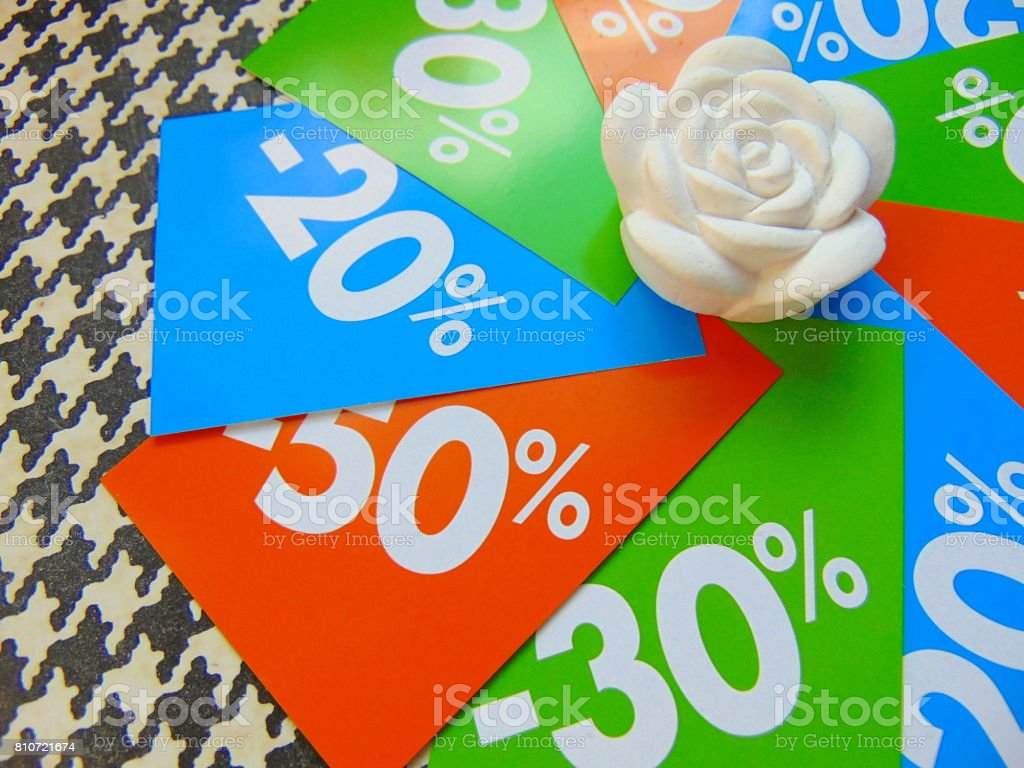 summer sale price tags in a circle around white flower stock photo