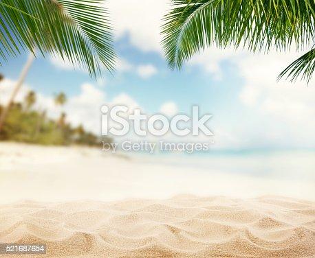 istock Summer sandy beach with blur ocean on background 521687654