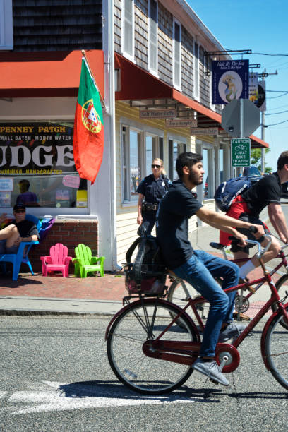 Summer scene, bicyclists on Commercial St., Provincetown, Cape Cod, New England, Massachusetts, USA stock photo