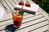 Summer Scene, Iced Tea with Lemon and mint on a garden table in bright sunshine.