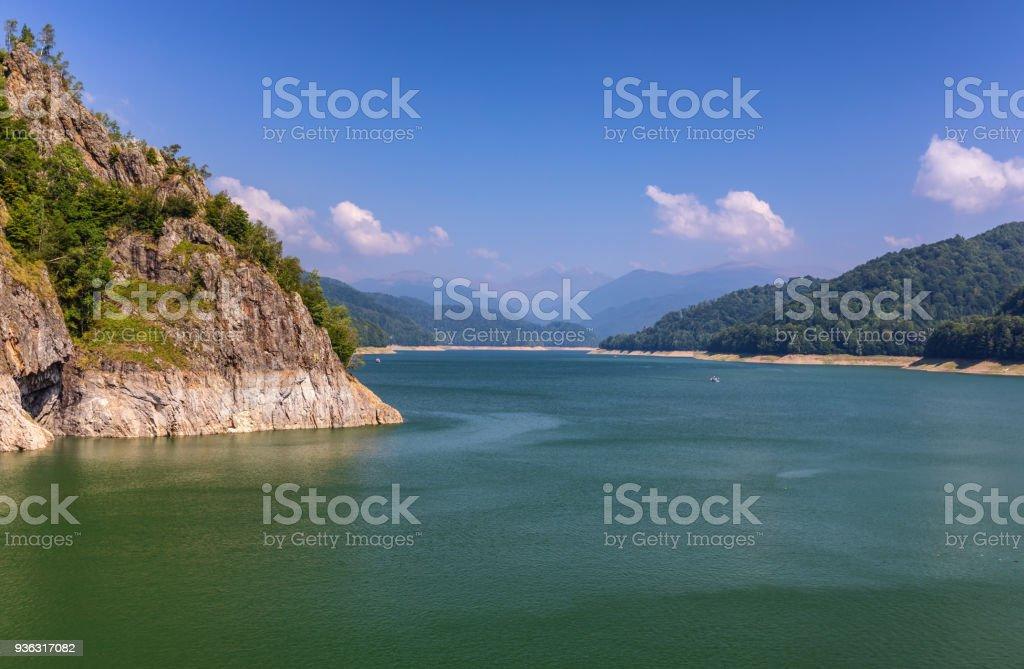 Summer scenery of Vidraru Dam and lake glowing in sunlight. Vidraru Dam, Romania. Carpathian Mountains, Fagaras ridge. stock photo