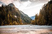 Summertime riverbed and woodland near Kranjska Gora in northwestern Slovenia with Julian Alps in background.