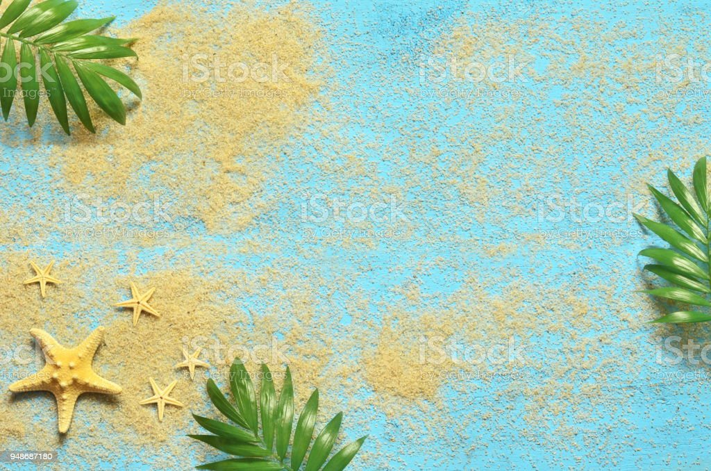 Summer sea background. Starfish and palm branch on a wooden blue background stock photo