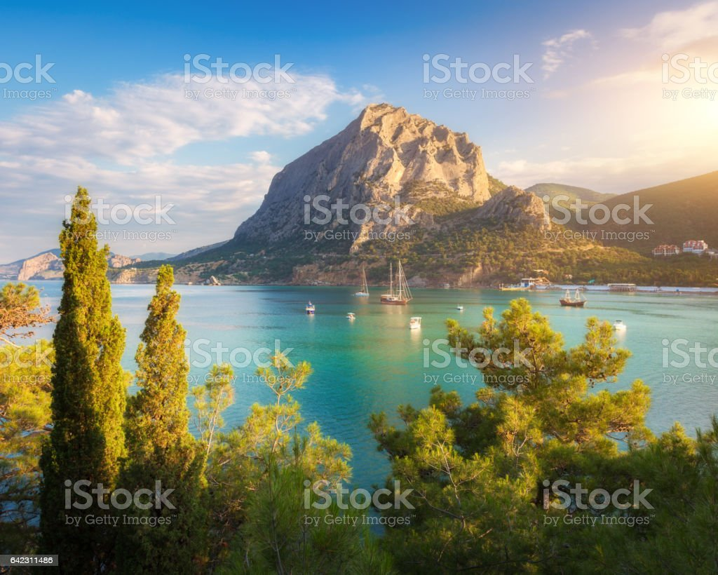 Summer seascape at sunset. Green trees against the sea, boats, mountains and blue sky with clouds and sunlight. Travel and nature background. Colorful landscape. Turquoise sea. Vacations in Crimea stock photo
