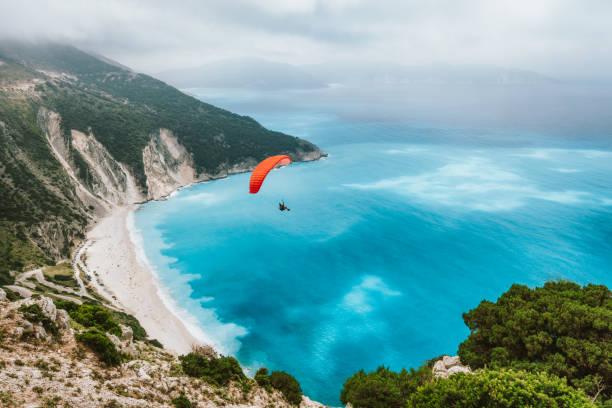 zomerseizoen activiteit. zweefvliegtuig dat over mooi strand myrtos vliegt. kefalonia eiland, griekenland. verbazingwekkende waterkleuren en bergkust - adrenaline stockfoto's en -beelden