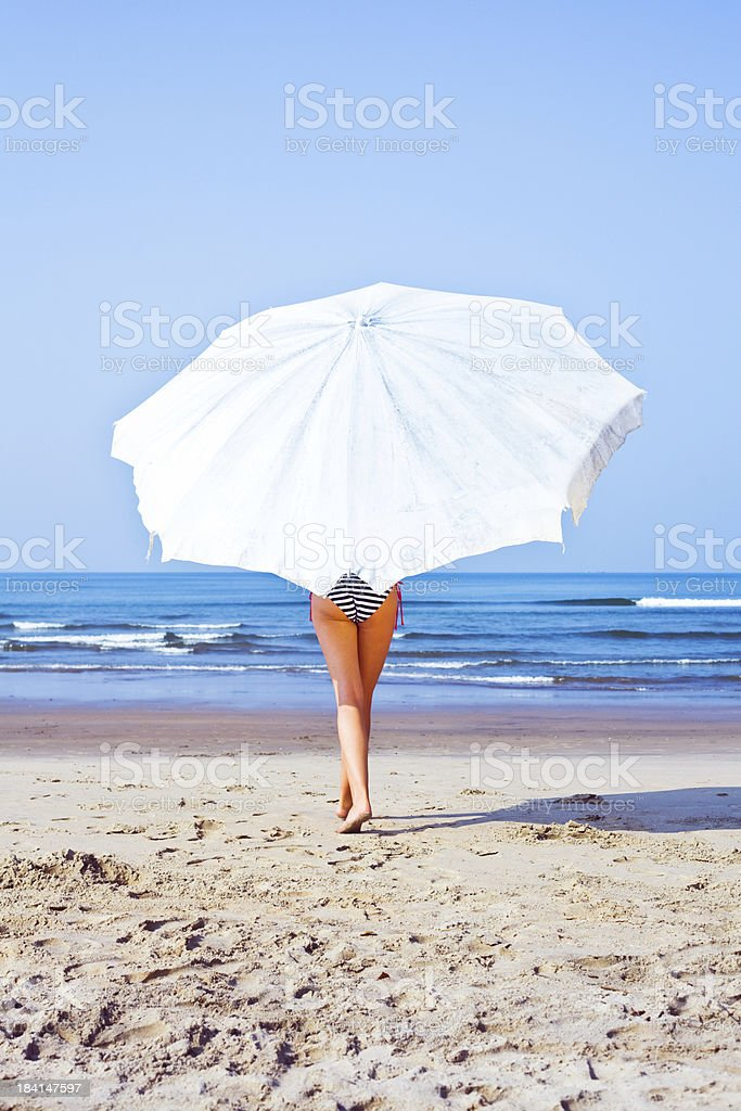 Summer season Sexy woman wearing striped bikini walking on a beach with white umbrella. Back view. Adult Stock Photo