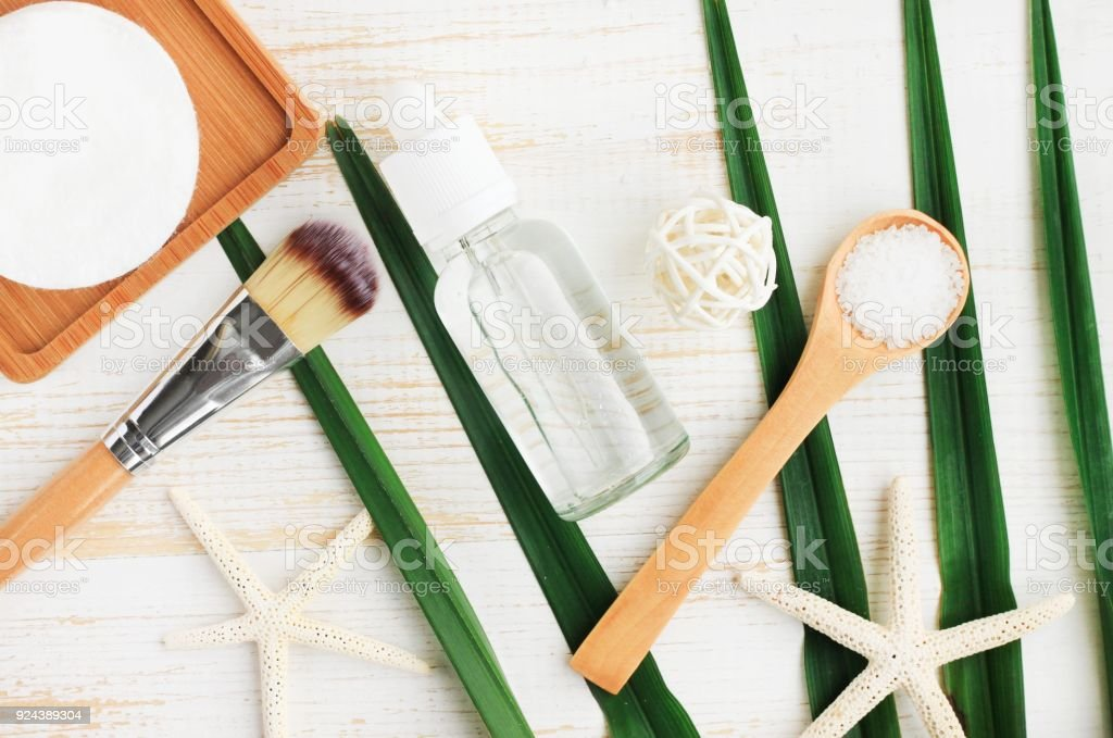 Summer skincare cosmetic product. Bottle of cleansing facial lotion, sea salt in spoon, green leaf stock photo