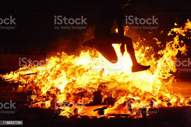 Photo of Summer solstice celebration in Spain. Woman jump. Fire flames