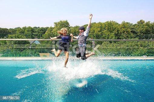 Fun couple jumping into pool. Woman looks like she is walking on water.