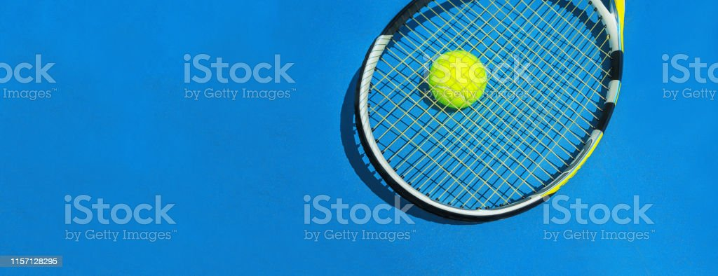 Summer sport concept with racket and tennis ball on blue hard tennis...