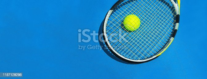 1153628111istockphoto Summer sport concept with racket and tennis ball on blue hard tennis court. 1157128295