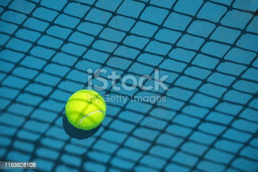 1153628111 istock photo Summer sport concept with tennis ball and net on hard tennis court. 1153628109