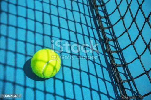 1153628111 istock photo Summer sport concept with tennis ball and net on hard tennis court. 1155237614