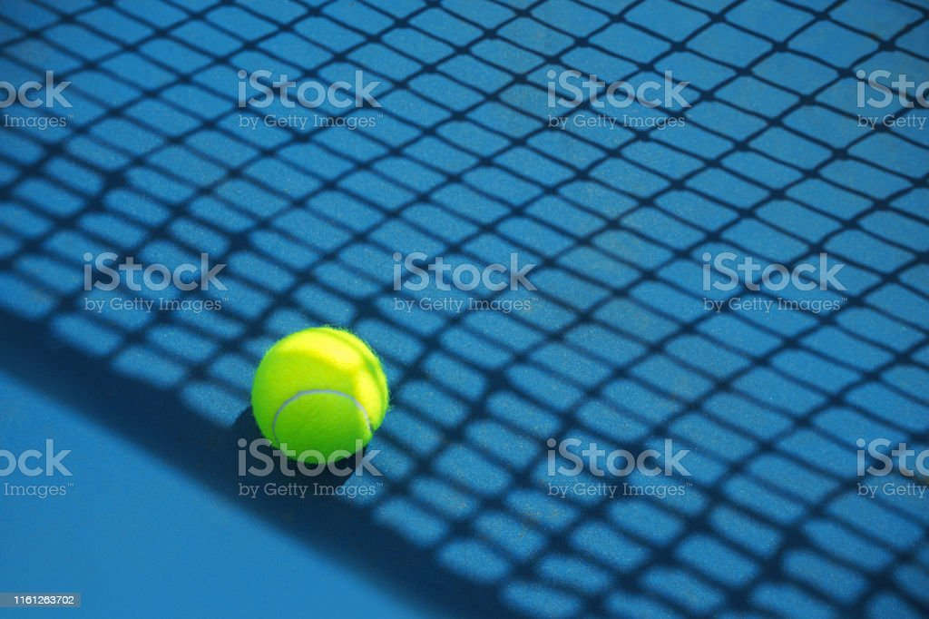 Summer sport concept with tennis ball and net on hard tennis court....